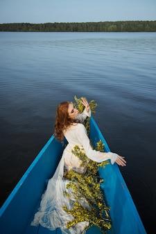 Рыжая женщина в белом платье неглиже сидит в синей лодке на пруду. рыжая девушка с желтыми цветочными ветками сидит в лодке на закате