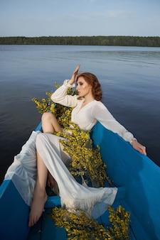 白いネグリジェのドレスを着た赤毛の女性は、池の湖の青いボートに座っています。日没時にボートに座っている黄色い花の枝を持つ赤い髪の少女