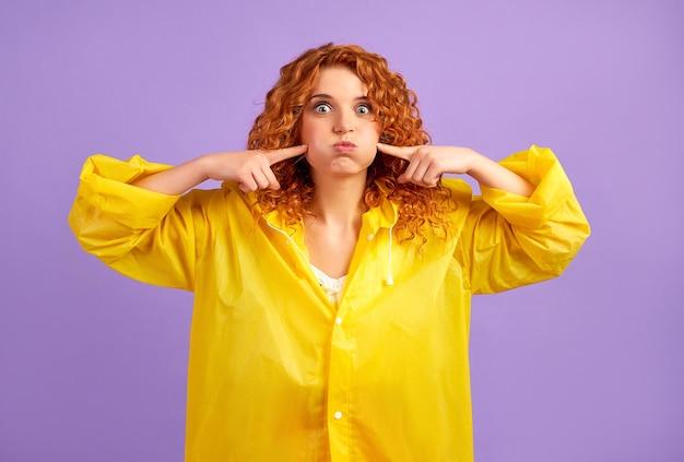 紫に分離された楽しみを持っている黄色のレインコートの赤毛の女性