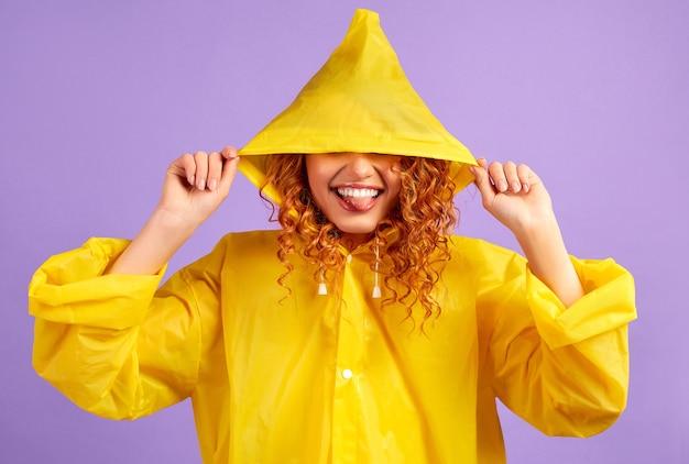 黄色のレインコートを着た赤毛の女性は、顔を紫に分離します