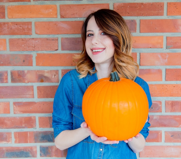 Redhead woman in jeans clothes holding orange autumn pumpkin