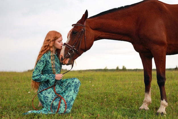 Redhead woman kissing her horse, autumn outdoors scene