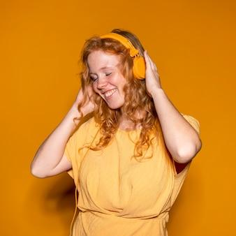 音楽を聴いている赤毛の女性