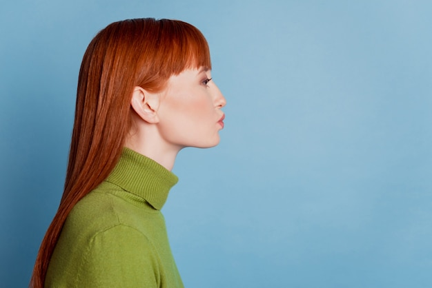 Redhead woman look empty space send air kiss isolated over blue background