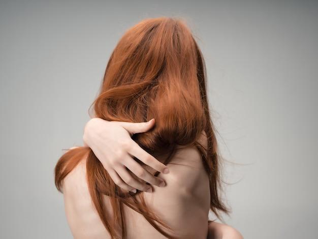 빨간 머리 여자 누드 백 깨끗한 피부 스튜디오 포즈. 고품질 사진