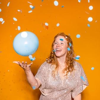 青い風船で遊ぶ赤毛の女性