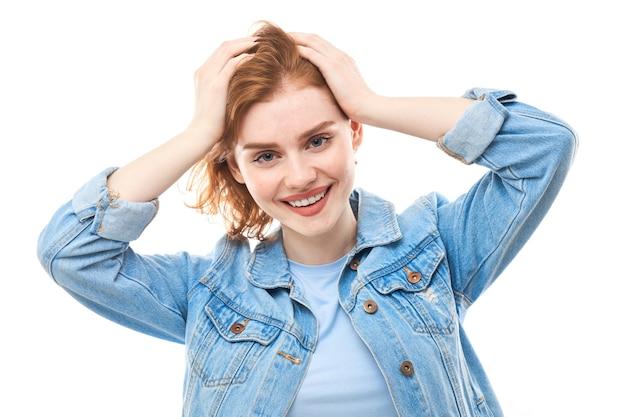 Портрет женщины redhead на белом изолированном фоне. держась за голову, он не может в это поверить. студентка
