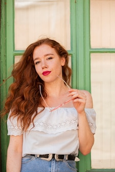 Redhead woman posing in front of  a window