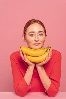 バナナの横にポーズをとる赤毛の女性