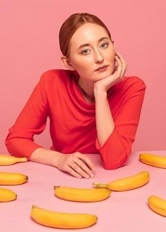 Рыжая женщина позирует рядом с бананами