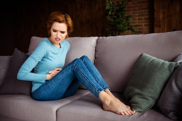 Рыжая женщина позирует на диване у себя дома