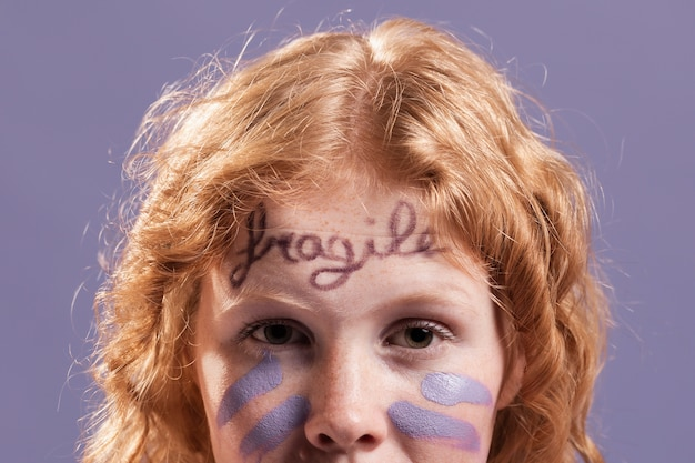 Redhead woman posing while being covered with dismissive words and paint