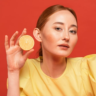 Рыжая женщина позирует с лимонами