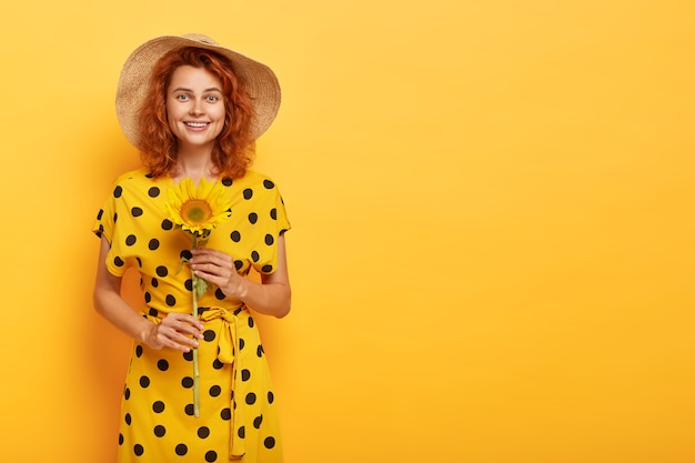 Redhead woman posing in yellow polka dress and straw hat