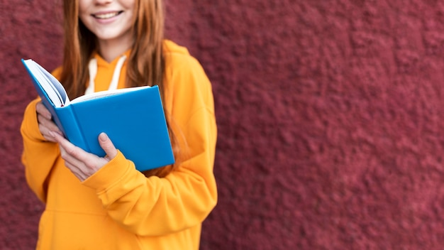Donna della testarossa che legge da un libro con lo spazio della copia