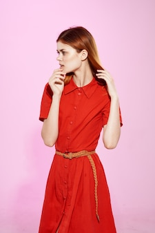 Рыжая женщина в красном платье позирует в студии.