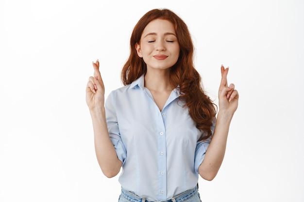 Donna dai capelli rossi sorridente speranzosa su bianco