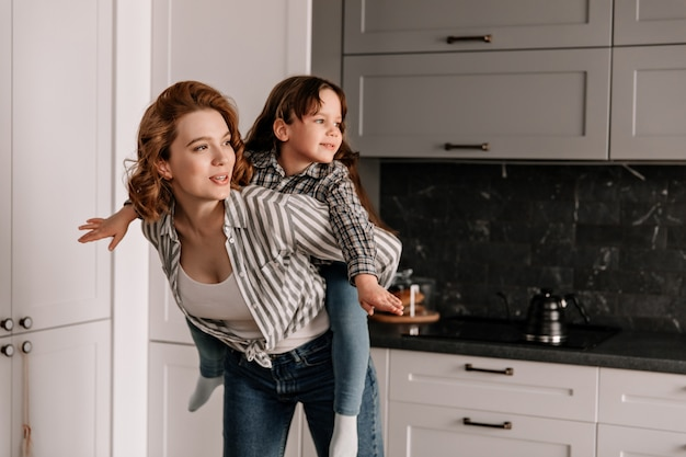 Redhead woman in striped shirt plays with her daughter and keeps her on her back.