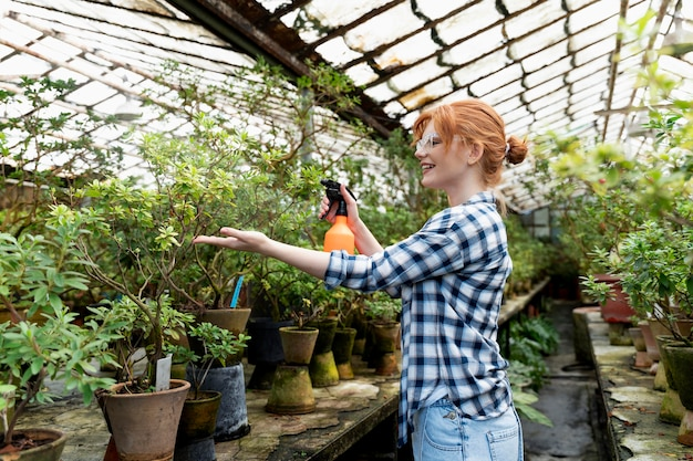 Donna dai capelli rossi che si prende cura delle sue piante in una serra
