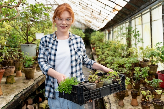 Redhead woman taking care of her plants in a greenhouse
