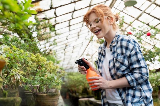 温室で彼女の植物の世話をしている赤毛の女性