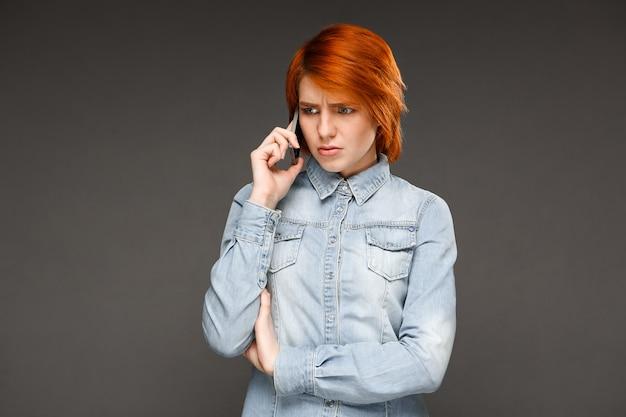 携帯電話で混乱して話している赤毛の女性