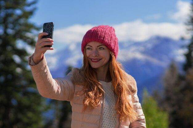 Рыжая женщина-путешественница в горном походе сфотографировала селфи на смартфоне