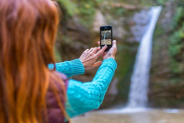 Рыжая женщина-путешественница в горном походе сфотографирована на смартфон