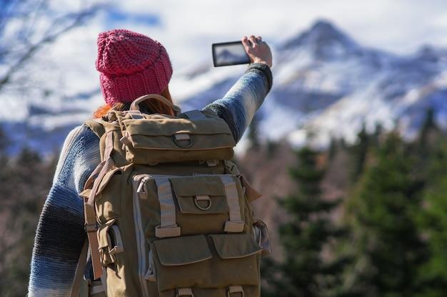Рыжая женщина-путешественница с рюкзаком в горном походе сфотографирована на смартфон
