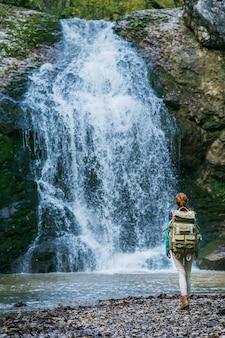 山のハイキングでバックパックと赤毛の女性旅行者