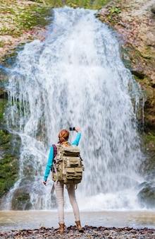 山のハイキングでスマートフォンで撮影されたバックパックを持つ赤毛の女性旅行者