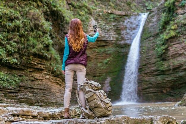 Рыжая женщина-путешественница с рюкзаком сфотографирована на смартфон в горном походе