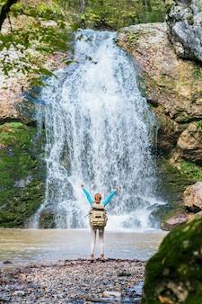 \バックパックを持つ赤毛の女性旅行者は山のハイキングで手を上げる