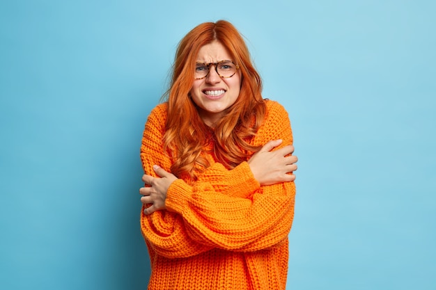 Redhead woman trembles from cold hugs herself to warm up walks outdoor during freezing temperature clenches teeth and shakes wears only sweater.