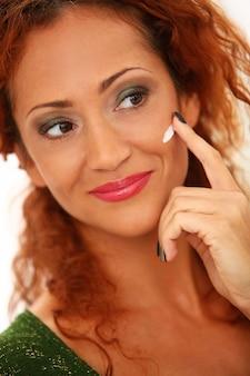 Redhead woman using facial cream