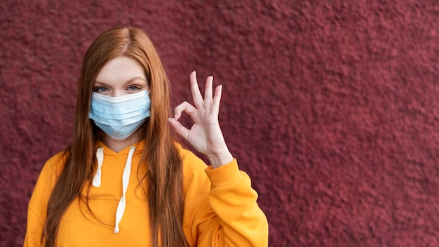 Redhead woman wearing a face mask with copy space