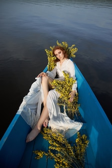 Redhead woman in white negligee dress sit in blue boat on pond lake. red-haired girl with yellow flower branches sitting in boat at sunset