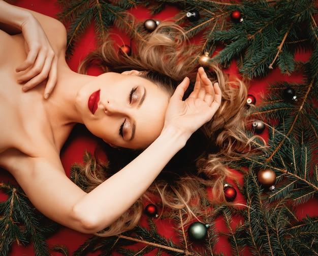 빨간 배경에 크리스마스 싸구려와 전나무 가지가 누워 있는 빨간 머리 여자