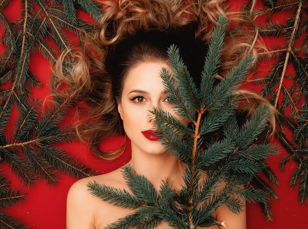빨간 배경에 전나무 가지가 누워 있는 빨간 머리 여자