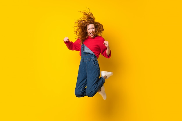 Redhead woman with overalls jumping over isolated yellow wall