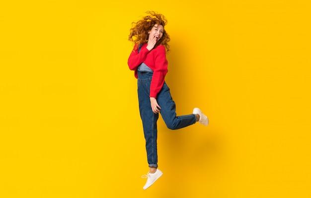 Рыжая женщина с комбинезоном, перепрыгивая через желтую изолированную стену