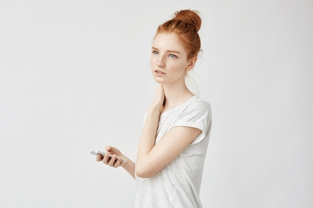Redhead woman with reckles holding phone thinking.