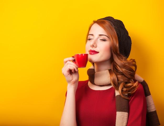 黄色の壁にコーヒーやお茶の赤いカップと赤毛の女性