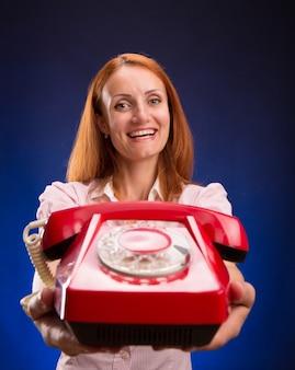 赤い電話を持つ赤毛の女性