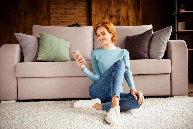 居間で屋内でポーズをとる短い髪の赤毛の女性