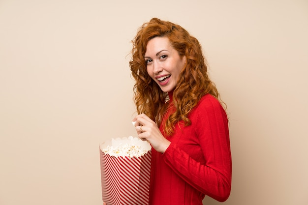 Redhead woman with turtleneck sweater eating popcorns