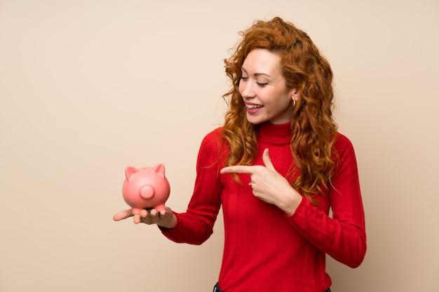 Redhead woman with turtleneck sweater holding a big piggybank