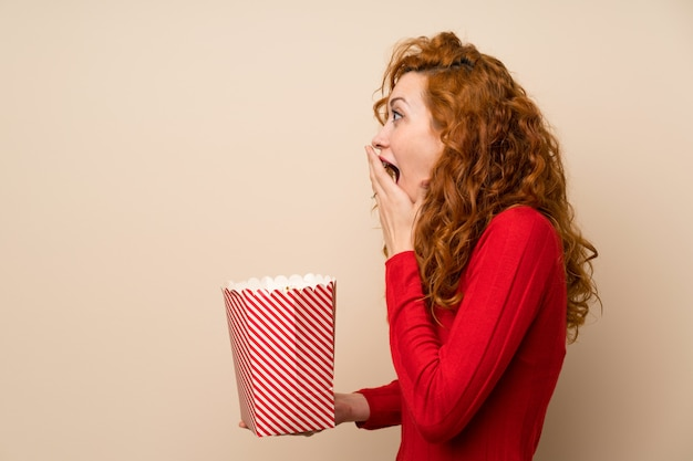 Redhead woman with turtleneck sweater holding a bowl of popcorns