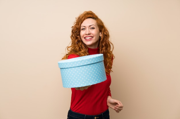 Redhead woman with turtleneck sweater holding gift box