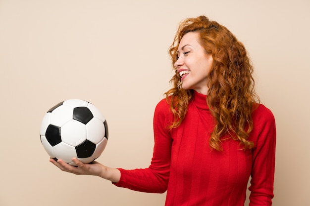 Redhead woman with turtleneck sweater holding a soccer ball